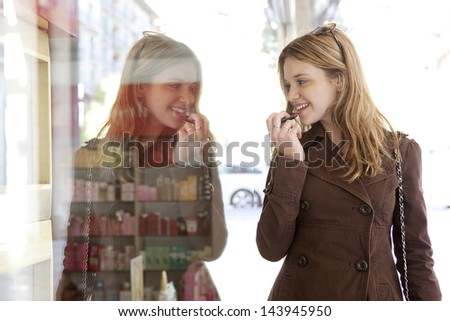 Close up side portrait of a young teenager tourist visiting the city and applying lipstick using the reflection of a shopping mall cosmetics store window. - stock photo