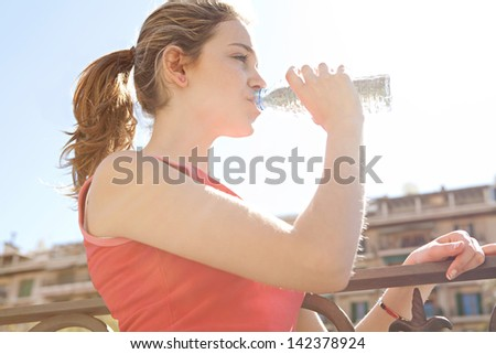 Close up side portrait of a young woman taking a break from exercising in the city, drinking from a blue plastic bottle of mineral water during a sunny morning run. - stock photo