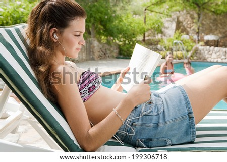 Close up side portrait view of a teenager girl relaxing and lounging during a summer holiday in a sunbathing lounger while reading a book and listening to music with headphones. Vacation lifestyle. - stock photo
