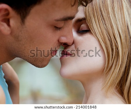 Close up side portrait view of a young tourist couple being romantic and kissing on the lips during a sunny summer day, outdoors. Emotions, feelings and first love romance. - stock photo