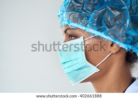Close up side profile of female surgeon in face mask getting ready for medical procedure surgery