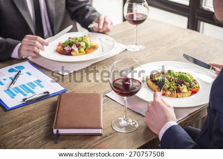 Close-up. Side view. Businessmen eating during a business lunch in restaurant. - stock photo