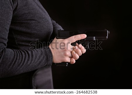 Close up side view of a gun pulled from holster on a black background - stock photo