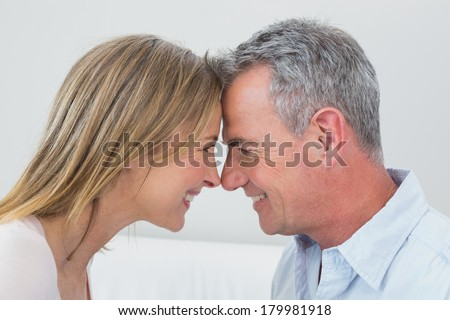 Close-up side view of a happy couple looking at each other at home - stock photo