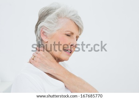 Close-up side view of a senior woman suffering from neck pain over white background - stock photo