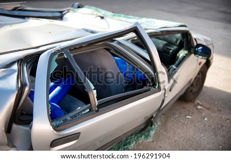 Close up side view of a silver motor car crumpled and destroyed in an accident with its windows blown out and shattered and roof caved in - stock photo