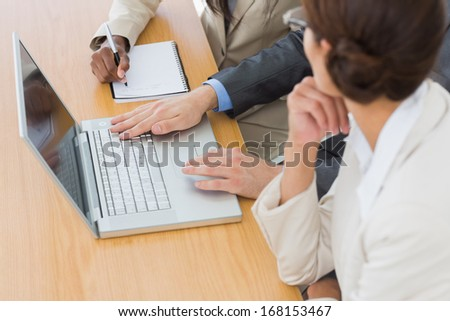 Close-up side view of business colleagues using laptop at office desk