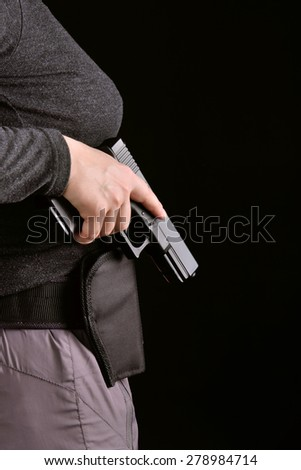 Close up side view of hand with a gun pulled from holster on a black background - stock photo