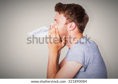 Close up side view of man blowing nose against grey background with vignette - stock photo