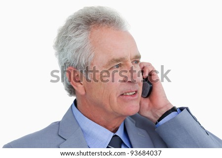 Close up side view of mature tradesman on his cellphone against a white background