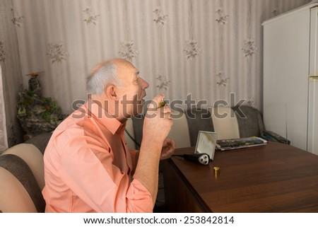 Close up Side View of Old Bald Man Spraying Aftershave on his Face After Cleaning his Beard While Sitting at the Sofa Inside the House. - stock photo