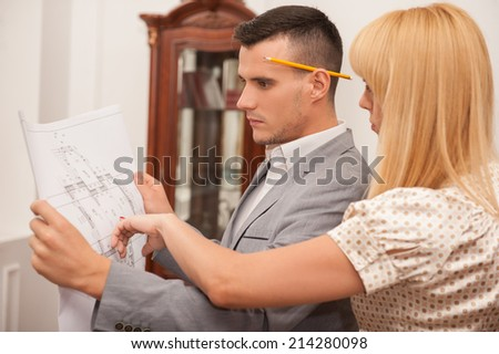 Close-up side view portrait of two young attractive architects discussing design project holding architectural plan in studio, classical interior background - stock photo