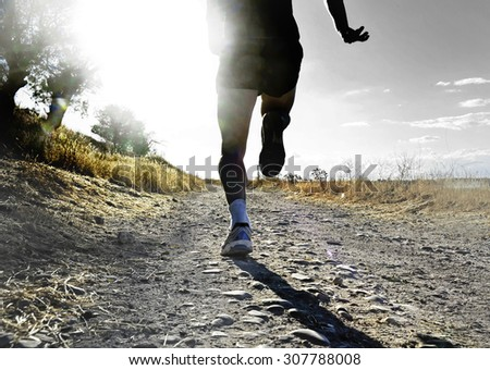 close up silhouette legs and feet of extreme cross country man running training on rural track jogging at sunset with harsh sunlight and lens flare in countryside sport and healthy lifestyle concept - stock photo
