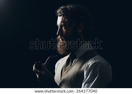 Close up Silhouette Man with Long Goatee Beard Holding a Smoking Pipe While Looking to the Left of the Frame on a Black Background. - stock photo