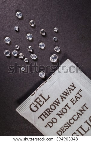 Close up silica gel or desiccant in paper bag on black background - stock photo