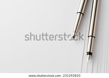 Close up Silver Pens and Blank Bond Papers on Top of White Table with Copy Space on the Left Side. - stock photo