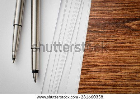 Close up Silver Pens and Blank White Paper Sheets on Top of Wooden Table with Copy Space for Texts. - stock photo