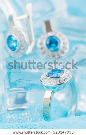 Close-up silver ring with zircon and expensive blue gemstone. Still life on ice blue background