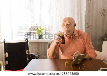 Close up Sitting Old Bald Man in orange Shirt Holding a Bottle Spray of Aftershave after Cleaning his Face at the Living Room. - stock photo