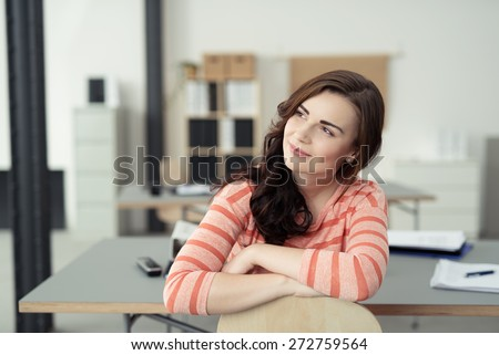 Close up Sitting Pretty Girl in Orange Stripe Shirt Leaning on a Chair While Looking to the Upper Left of the Frame and Thinking of Something. - stock photo