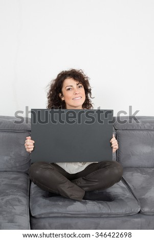 Close up Sitting Young Woman Holding Black. Cardboard .Woman holding black cardboard while Looking at the Camera.