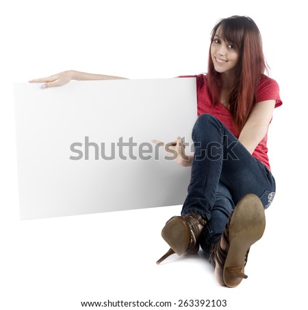 Close up Sitting Young Woman in Trendy Attire Pointing at her Empty White Large Cardboard, Emphasizing Copy Space, While Looking at the Camera, Isolated on White Background.