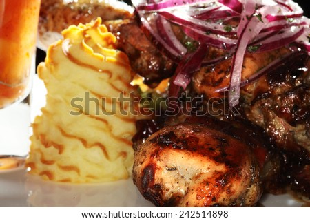 close-up skewers of meat garnished with potato gratin and greens