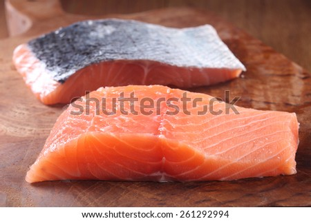Close up Slice of Raw Fresh Fish Meat on Wooden Chopping Board on Top of the table. - stock photo