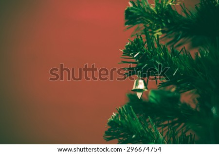 close up small bell on christmas tree on red background vintage style - stock photo