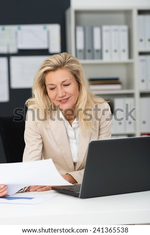 Close up Smiling Adult Office Woman, with Blond Hair, Reading Document at her Office with Laptop on the Table. - stock photo