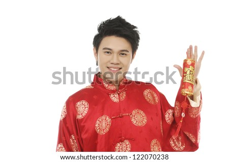 Close up smiling chinese young man with tradition clothing holding lucky Symbol - stock photo