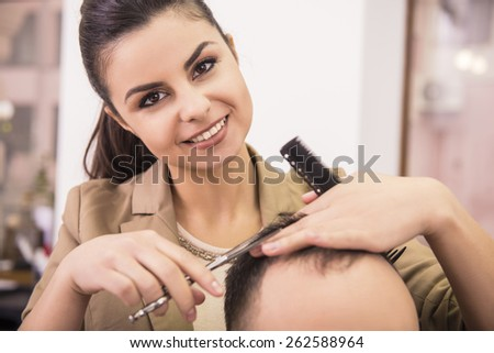 Close-up smiling female hairdresser is cutting hair of man client. - stock photo