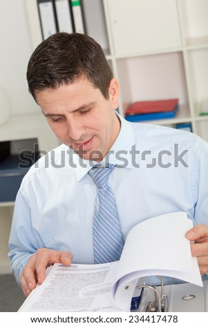 Close up Smiling Good Looking Businessman Reading Report Documents at his Office with Cabinet at his Background.