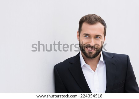 Close up Smiling Handsome Middle Age Businessman in Black and White Suit Leaning on White Wall. - stock photo