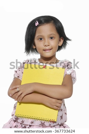 Close up-Smiling little girl holding notebook
