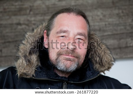 Close up Smiling Middle Age Man with Goatee Beard Wearing Fur Lined Black Hooded Coat Looking at Camera. - stock photo