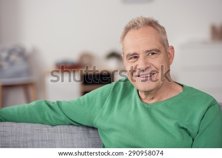 Close up Smiling Middle Aged Man in Casual Green Shirt, Sitting at the Sofa While Looking Into Distance and Thinking of Something - stock photo