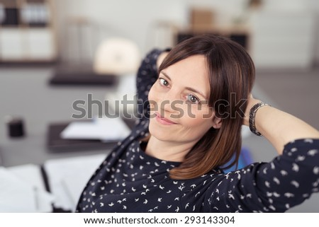 Close up Smiling Office Woman Relaxing at her Desk While Leaning her Back in a Chair and Looking at the Camera. - stock photo