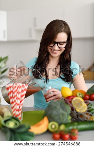 Close up Smiling Pretty Girl at the Kitchen, Pouring Organic Juice from a Blender on a Glass Behind Healthy Fresh Fruits and Vegetables. - stock photo