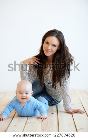 Close up Smiling Pretty Mother and Adorable Baby Having Quality Time at Home. Captured in White Wall Background. - stock photo