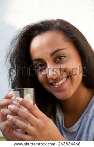 Close up Smiling Pretty Young Woman Holding a Glass of Water with her Both Hands while Looking at the Camera. - stock photo