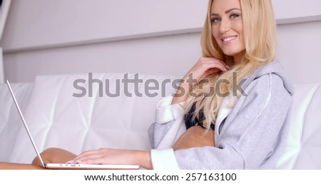 Close up Smiling Sexy Woman with Blond Hair  Wearing a Gray Sleep Robe  Sitting on a White Couch with Laptop on her Lap While Looking at the Camera. - stock photo