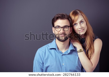 Close up Smiling Young Business Couple Against Gray Wall with Copy Space, Looking at the Camera.
