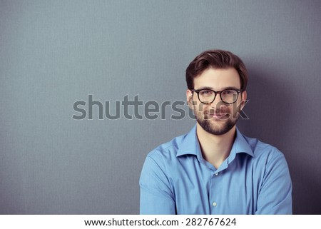 Close up Smiling Young Businessman Wearing Eyeglasses, Looking at the Camera Against Gray Wall Background with Copy Space - stock photo