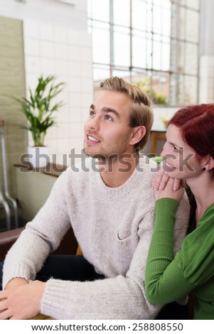 Close up Smiling Young White Couple Having Sweet Moments at Living Room while Man Looking Up, Emphasizing Recalling. - stock photo