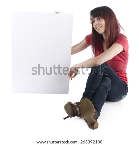 Close up Smiling Young Woman Sitting on the Floor in Casual Clothing Showing Blank White Cardboard with Text Space, Isolated on White Background.