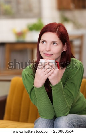 Close up Smiling Young Woman with Burgundy Hair, Wearing Green Long Sleeve Tops, Sitting on Sofa with a Cup of Coffee. Looking Up Emphasizing Day Dreaming. - stock photo