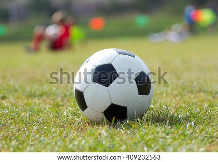 Close-up soccer ball on green grass and coach children