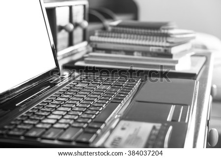 Close-up, soft focus keyboard with pile of books, selective focus, shallow depth of field, black and white monochrome - stock photo