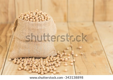 Close up soy beans in sack on wooden desk - stock photo